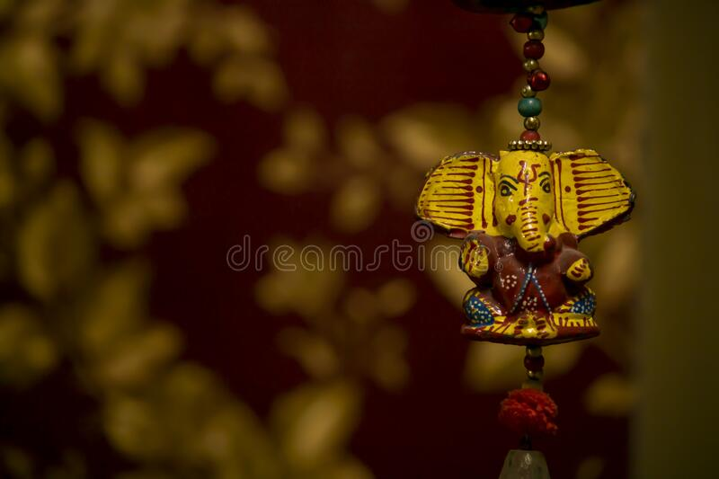 Lord ganesha hanging handicraft with blurred red and gold background stock image
