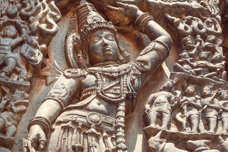 Lord Krishna com uma mão aumentou sobre o ser humano, no relevo do templo indiano sul do século XII Herança de Halebidu, Índia foto de stock