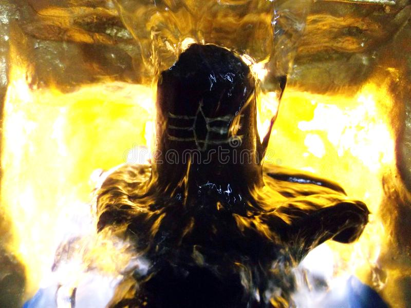 Lord shiva lingam in water bath golden hill with fire. My own creation project from water fountain lord shivalingam golden hill royalty free stock images