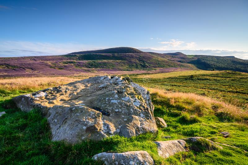Lordenshaws Prehistoric Rock mirrors Simonside Hills Ridge. Lordenshaws Hillfort is located near Rothbury in Northumberland National Park and has several large royalty free stock images
