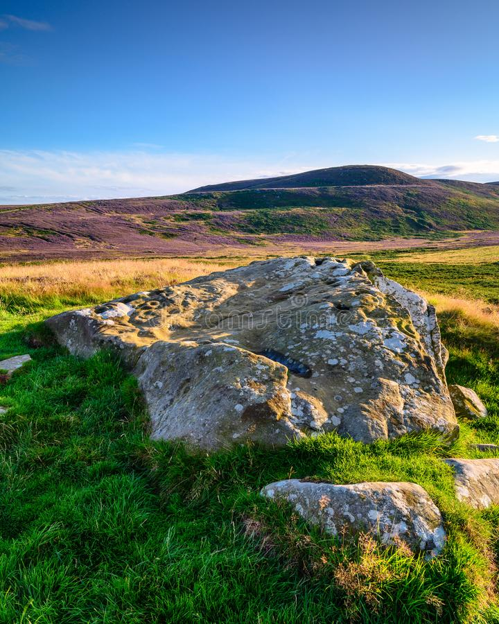 Lordenshaws Prehistoric Rock and Simonside Hills portrait. Lordenshaws Hillfort is located near Rothbury in Northumberland National Park and has several large royalty free stock image