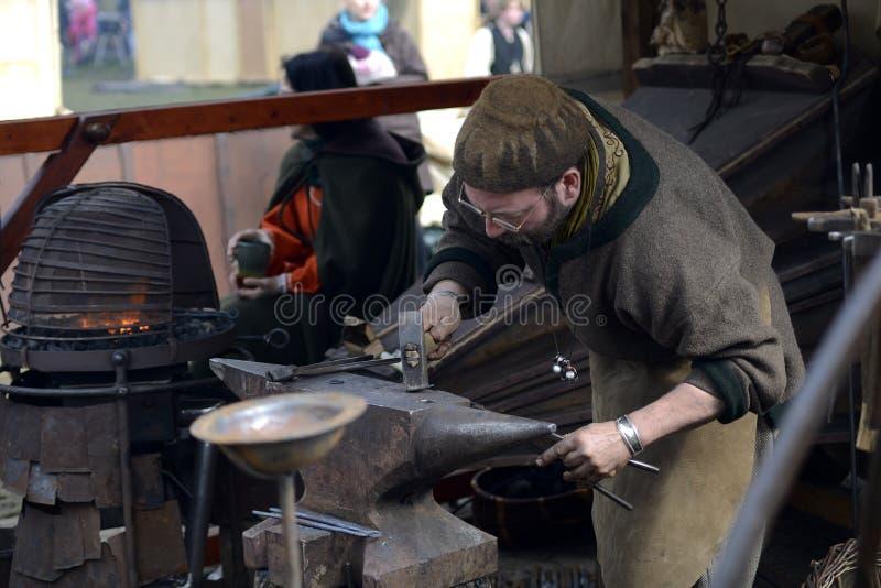 06 04 Lorelay 2015 Germania - metallo di lavoro del fabbro con il martello sull'incudine nella forgia fotografia stock libera da diritti