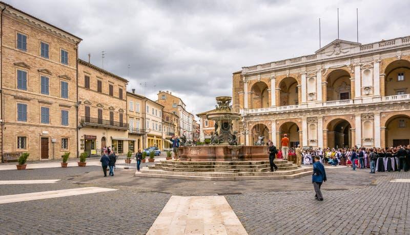 LORETO, marços, Itália - juli 16, 2016: A fonte de pedra medieval com dragões de bronze, no quadrado de Madonna com o apostólico imagem de stock royalty free