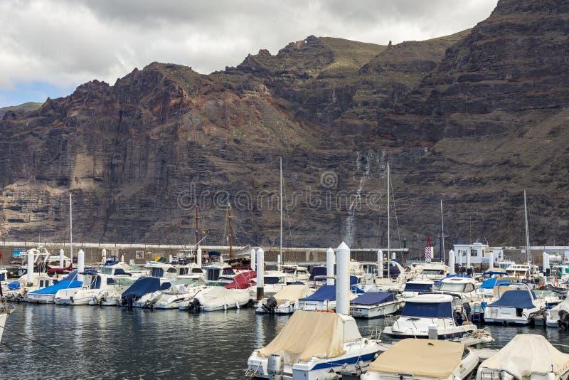 Los癸干忒斯西班牙 03-05-2019 在巨大的峭壁前面的港口在Los癸干忒斯镇在特内里费岛 r 免版税库存图片