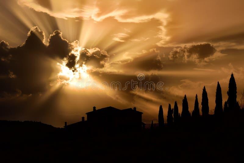 Los árboles de ciprés famosos de Toscana con la casa del granjero en puesta del sol con el rayo se encienden imagenes de archivo