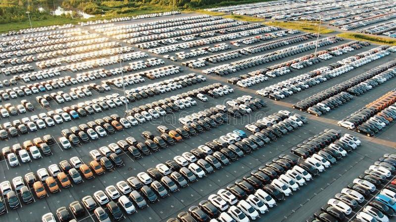 Los árboles enormes del estacionamiento del almacén de la fábrica del coche reflejan en el lago fotos de archivo