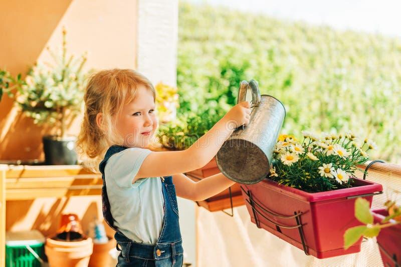Los 3-4 años adorables embroman a la muchacha que riega las flores amarillas de la margarita en balcón soleado imagen de archivo