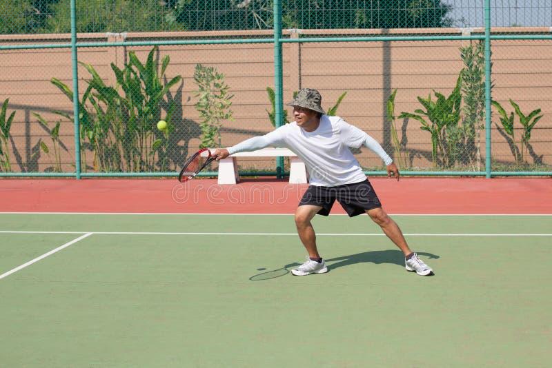 Los años mayores 59s sirven jugar a tenis en club de deporte fotografía de archivo libre de regalías