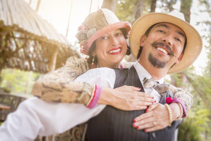 los años 20 vistieron los pares románticos que ligaban al aire libre foto de archivo libre de regalías