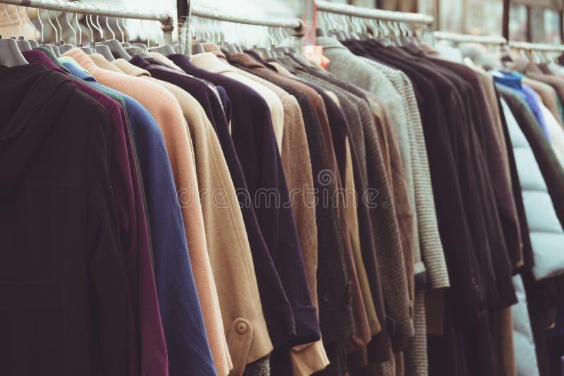 Los abrigos de invierno del foco selectivo colgaron en un estante de la ropa imagenes de archivo