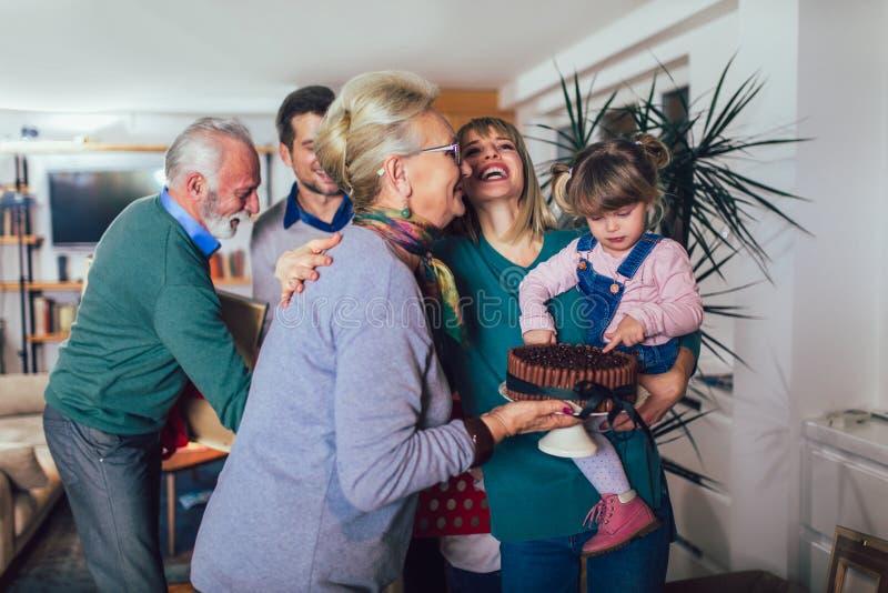 Los abuelos traen un regalo para trasladarse a un nuevo apartamento a sus niños fotos de archivo libres de regalías