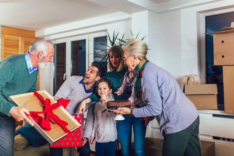 Los abuelos traen un regalo para trasladarse a un nuevo apartamento a sus niños fotografía de archivo libre de regalías