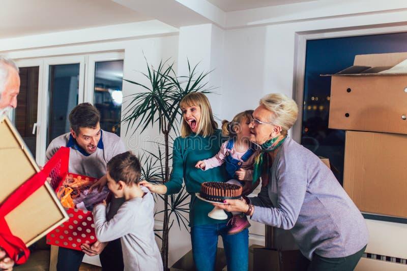 Los abuelos traen un regalo para trasladarse a un nuevo apartamento a sus niños imagenes de archivo