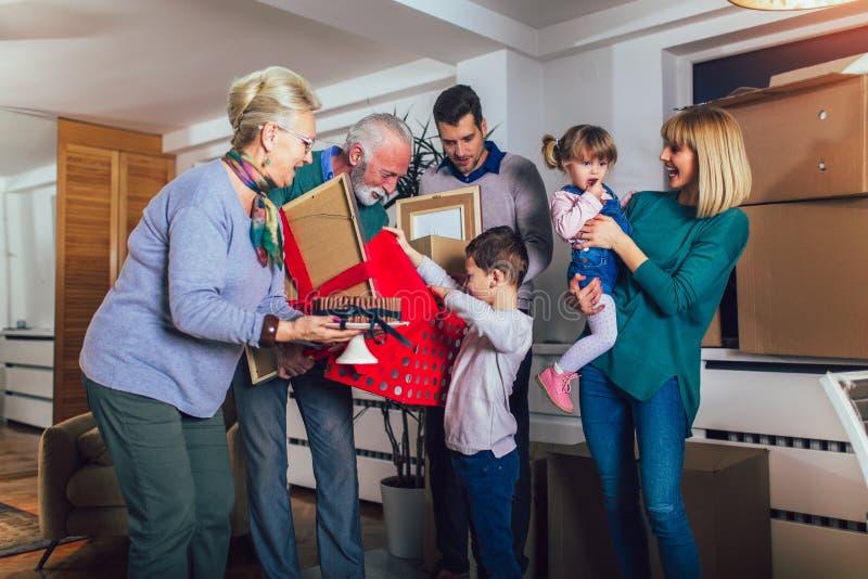 Los abuelos traen un regalo para trasladarse a un nuevo apartamento a sus niños fotos de archivo