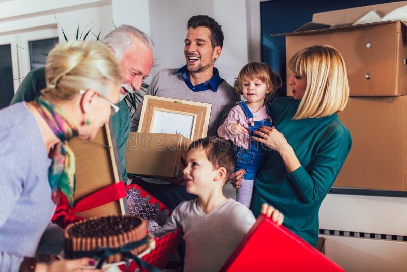 Los abuelos traen un regalo para trasladarse a un nuevo apartamento a sus niños foto de archivo libre de regalías