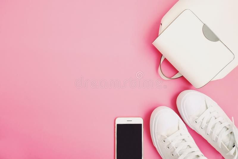 Los accesorios de la mujer blanca hacen excursionismo, las zapatillas de deporte, llaman por teléfono a endecha plana en fondo ro fotos de archivo