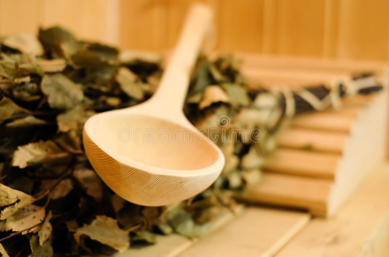 Los accesorios de la sauna se cierran para arriba en sauna finlandesa o rusa tradicional, escoba de abedul y cucharada de madera  fotografía de archivo libre de regalías