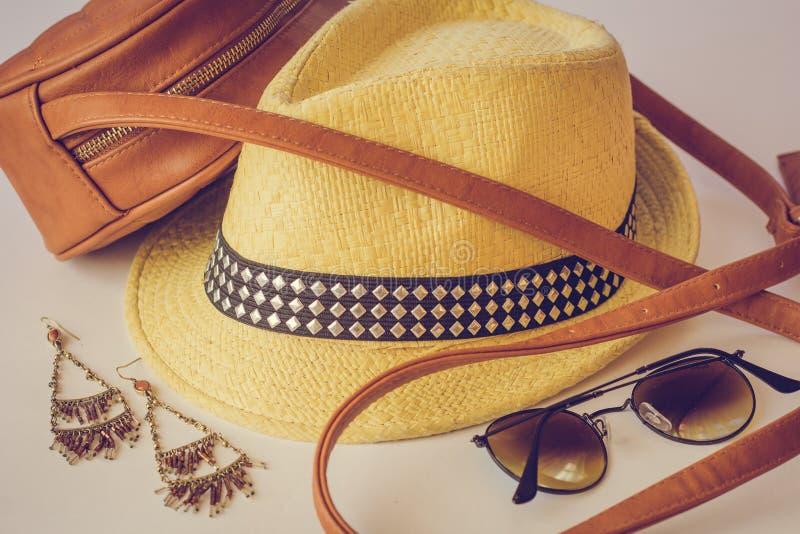 Los accesorios del verano, un bolso, un sombrero de paja, las gafas de sol y los pendientes mienten en la tabla Cuatro accesorios fotografía de archivo libre de regalías