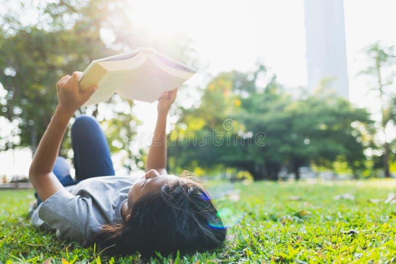 Los adolescentes asiáticos son libros de lectura de mentira imagenes de archivo