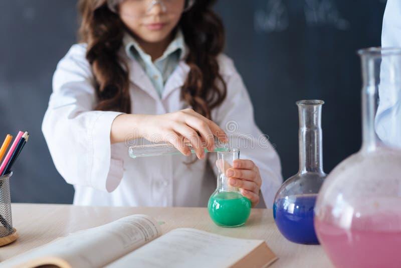 Los adolescentes capaces que participan en la química experimentan en la escuela imagenes de archivo