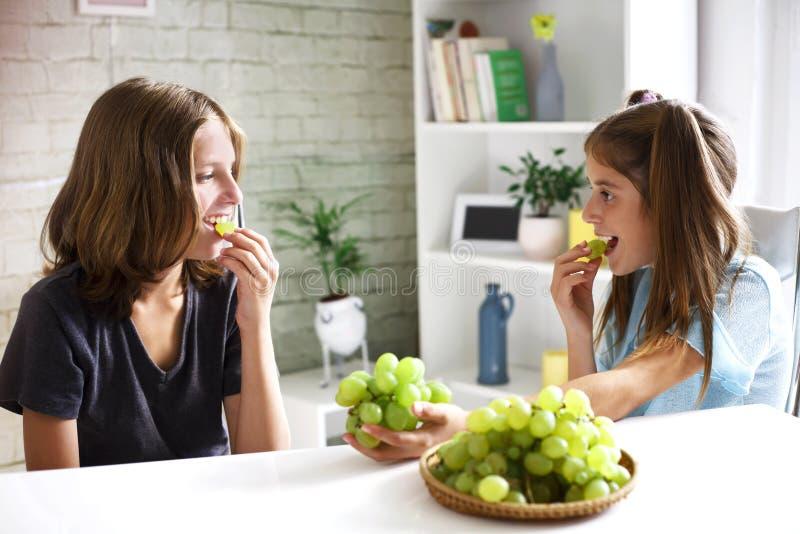 Los adolescentes comen las uvas orgánicas frescas imágenes de archivo libres de regalías