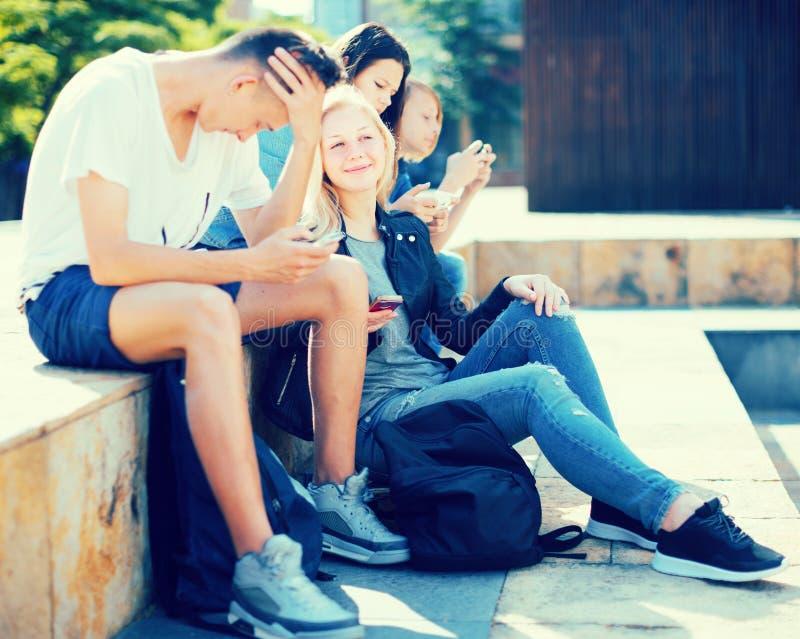 Los adolescentes comunican en patio imagenes de archivo