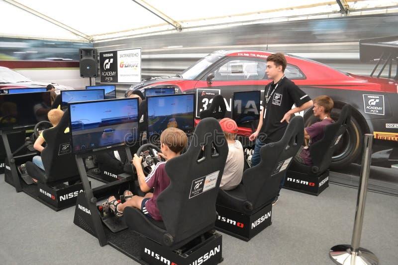 Los adolescentes conducen los simuladores de competir con el juego en la G-impulsión S de Nismo fotografía de archivo libre de regalías