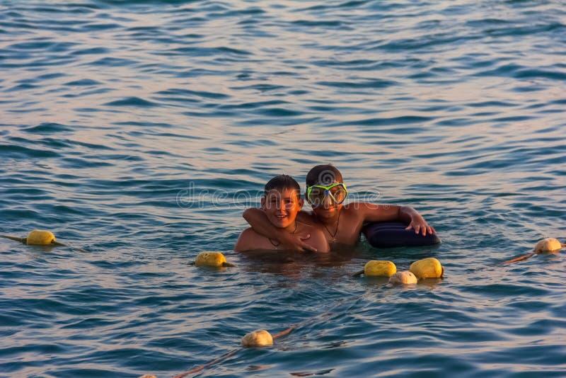 Los adolescentes de los muchachos 12-15 años nadan en el mar en un verano fotografía de archivo libre de regalías