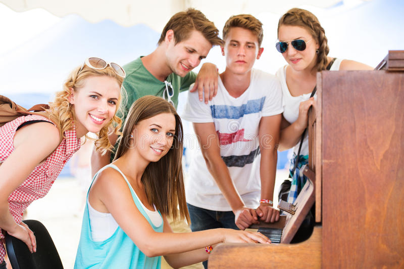 Los adolescentes en el festival de música del verano, muchacha juegan el piano fotos de archivo libres de regalías