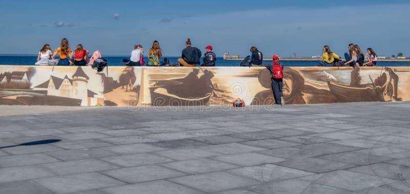 Los adolescentes en la costa se están sentando en una pared foto de archivo
