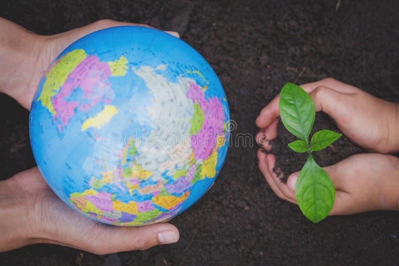 Los adultos que llevan a cabo una mano del globo y del niño que sostiene un pequeño almácigo, planta un árbol, reducen el calenta foto de archivo libre de regalías