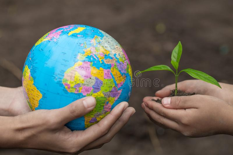 Los adultos que llevan a cabo una mano del globo y del niño que sostiene un pequeño almácigo, planta un árbol, reducen el calenta foto de archivo