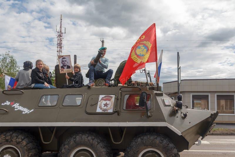 Los adultos y los niños en un vehículo blindado de transporte de personal participan en desfile en honor de la victoria DA imagen de archivo libre de regalías