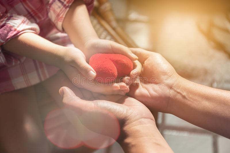 Los adultos y los niños están llevando a cabo un corazón rojo fotos de archivo libres de regalías