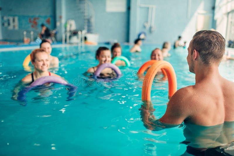 Los aeróbicos de la aguamarina, mujeres clasifican con el instructor masculino imagen de archivo