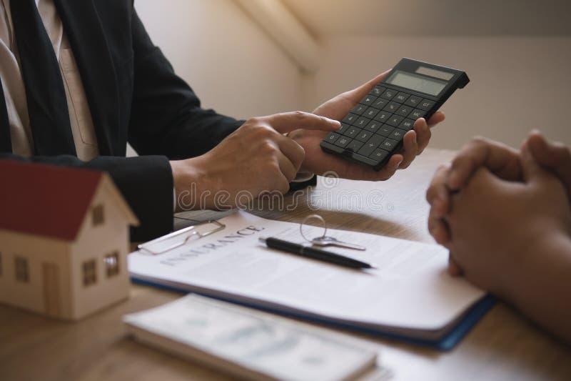 Los agentes calculan el tipo de pago del préstamo o el importe de las primas de seguro para los clientes que se ponen en contacto fotografía de archivo