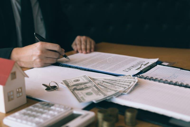 Los agentes de casa del vendedor proporcionan dominante a los nuevos due?os de la casa en oficina imagen de archivo libre de regalías