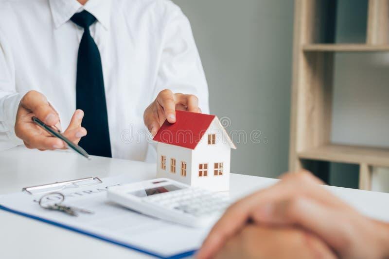 Los agentes de casa del vendedor proporcionan dominante a los nuevos due?os de la casa en oficina imagen de archivo