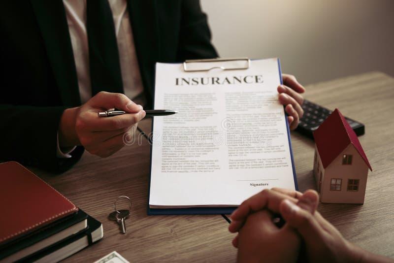 Los agentes utilizan bolígrafos que apuntan a los contratos de seguro y se explican a los clientes de la oficina fotografía de archivo