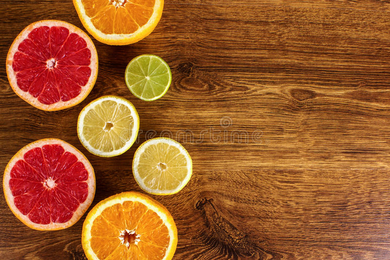Los agrios cortaron las naranjas del fondo, limones, cales, pomelo en un fondo de madera foto de archivo
