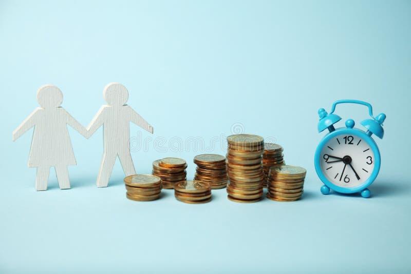 Los ahorros de la familia, el tiempo y el dinero, figuras de los padres la pareja de matrimonios imagen de archivo libre de regalías