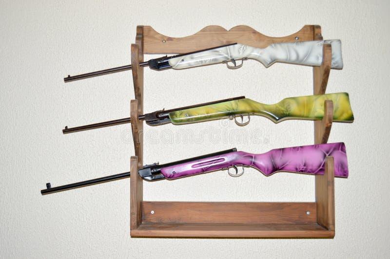 Los airguns viejos airbrushed coloridos a disposición hicieron el estante de arma a mano imagen de archivo