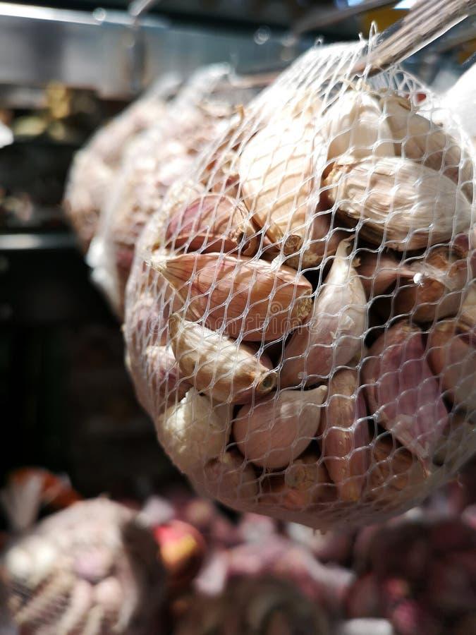 Los ajos pelados embalaron en un bolso de la malla en venta en supermercados foto de archivo libre de regalías