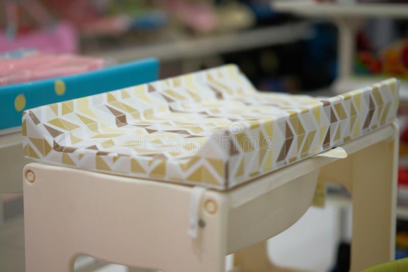 Los ajustes que cambian el cojín presentan el colchón de la cama de bebé, cambio del pañal del bebé fotografía de archivo libre de regalías