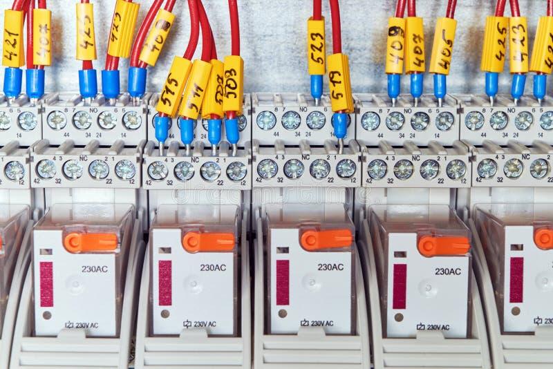 Los alambres eléctricos o los cables están conectados con una retransmisión intermedia según el esquema foto de archivo
