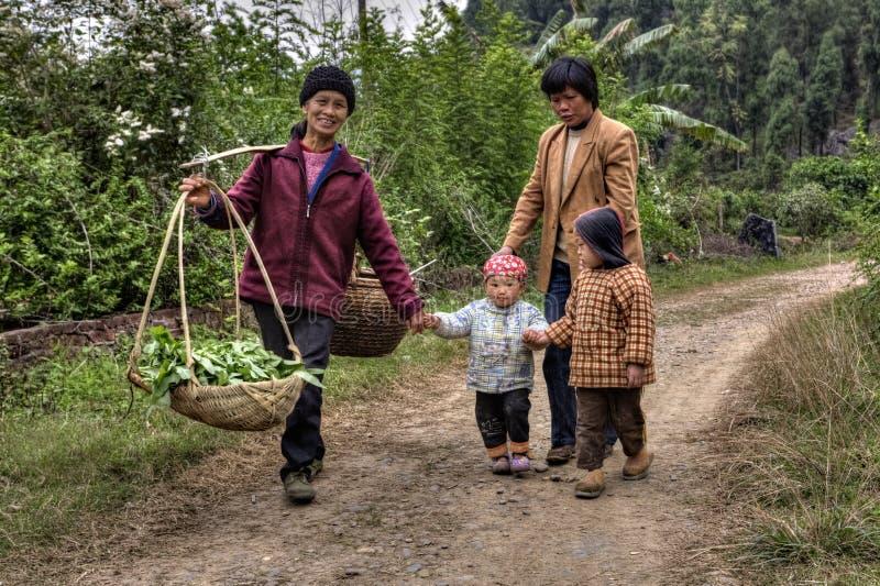 Los aldeanos en China, mujeres con los niños, están en la carretera nacional fotos de archivo