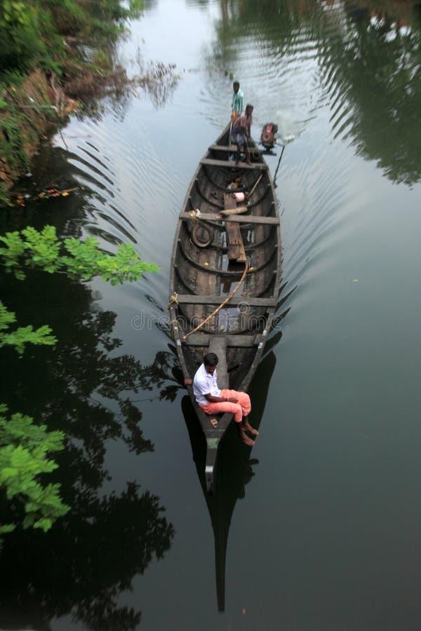 Los aldeanos reman un bote pequeño para viajar a través de los remansos fotografía de archivo