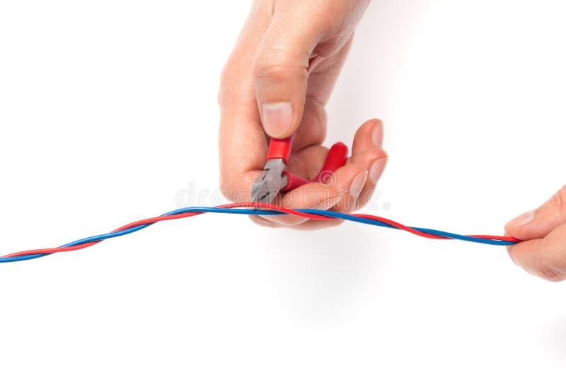 Los alicates del corte del alambre cortan el rojo imagenes de archivo