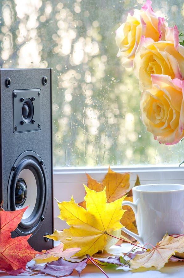 Los altavoces de audio y las rosas amarillas con las hojas de arce acercan a la ventana fotos de archivo