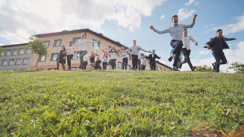 Los alumnos mayores felices corren de la colina en el fondo de su escuela fotos de archivo